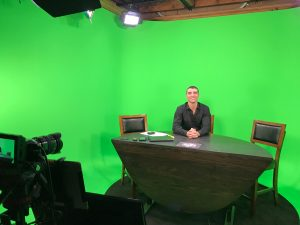 Fletcher sitting at a desk in front of a green screen.