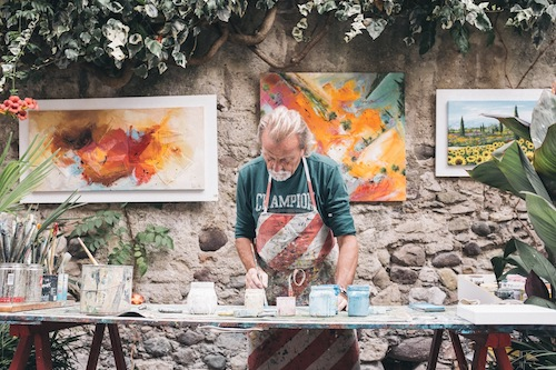 Man painting on a table with a stone wall behind him