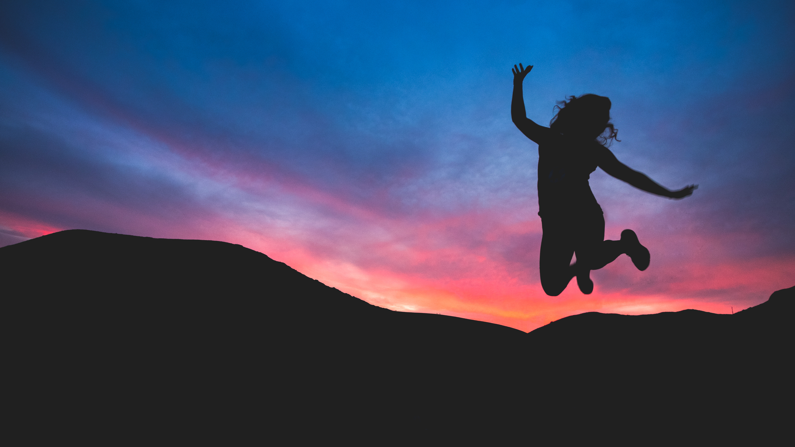 Silhouette of a woman jumping against a sunset