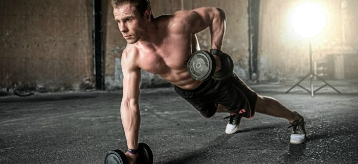 A very fit man doing a plank with weights