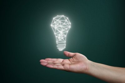 glowing light bulb hovering over someone's palm with a green background