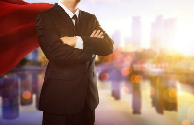 superhero businessman looking at city skyline at sunset.