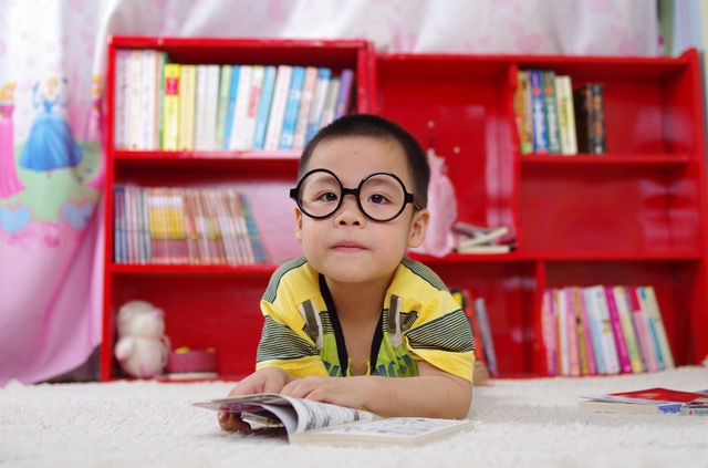 Kid sitting and reading a book with big round black glasses