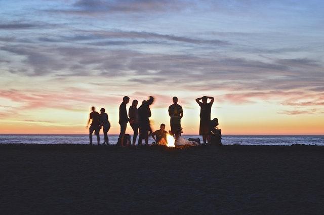 Friends on a beach having a bonfire