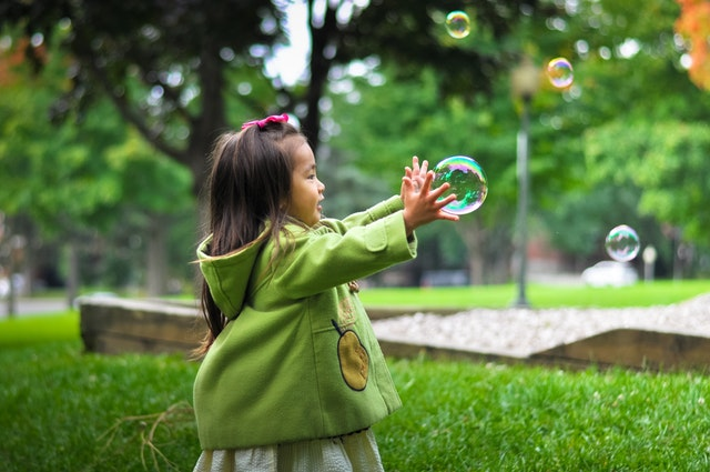 Little girl reaching for a bubble