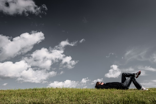 Person laying in the grass looking up at the sky
