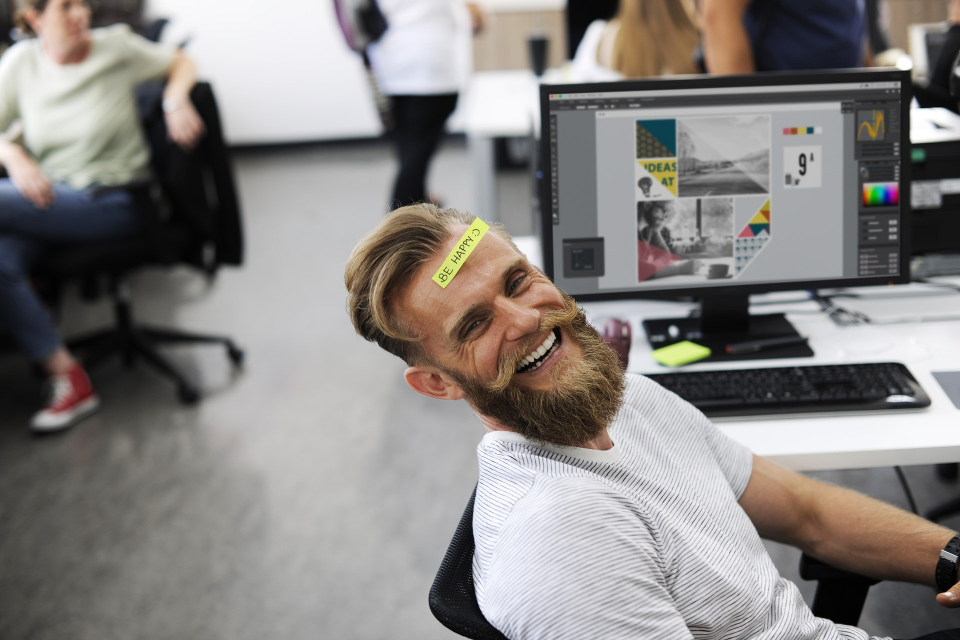 "Man sitting at an office desk smiling with a sticky note on his forehead that says ""Be Happy"""