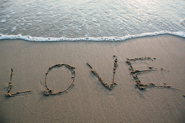 The word love carved into sand on the beach