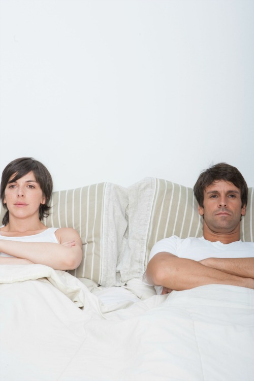 Couple laying in bed with arms crossed and looking away from each other