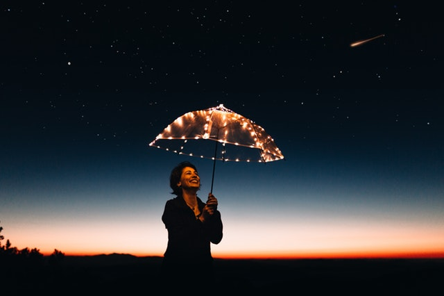 Woman standing with a light-up umbrella above her head