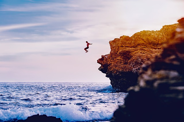 Person jumping off a cliff into the ocean