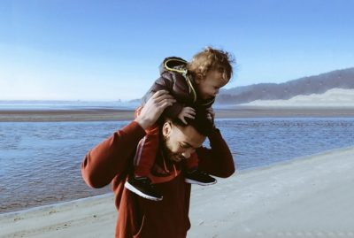 A dad holding his kid on his shoulders on the beach