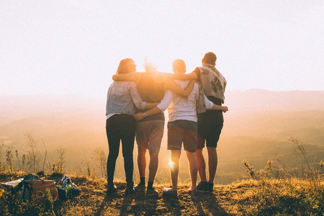 Group of friends with their arms around each other on a mountain