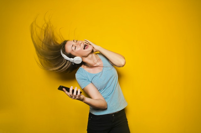 Woman listing to music and dancing against a yellow backdrop