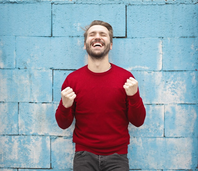 Man in a red sweater against a blue wall smiling