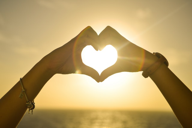 Hands making a heart over a sunset