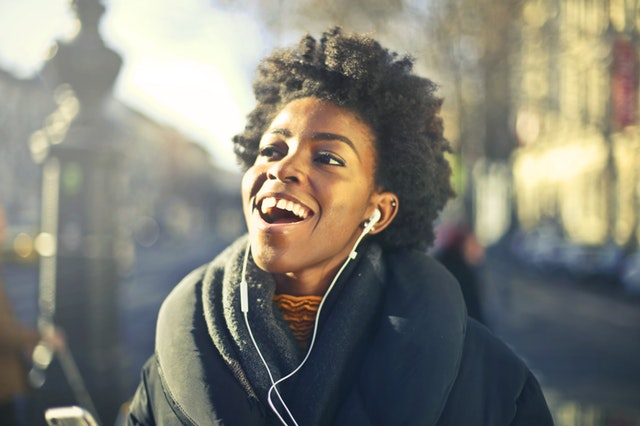 Woman walking down the street listening to music and smiling