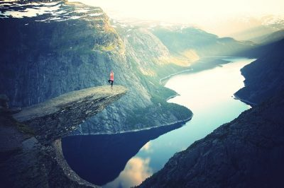 Woman doing yoga on a rock over a canyon