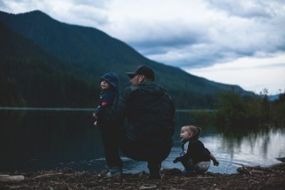 Man with two kids by a lake