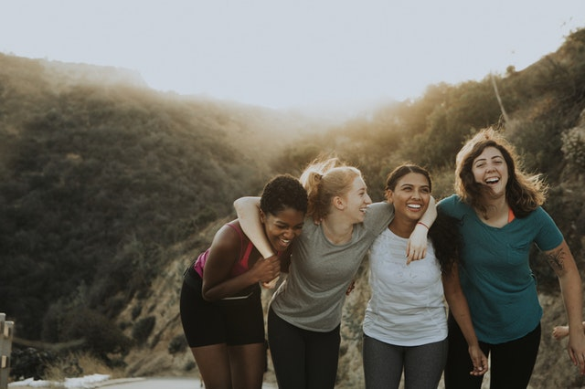 Women hiking and hugging