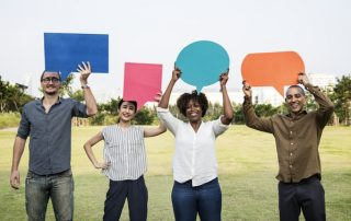 Four people standing and holding speech bubbles