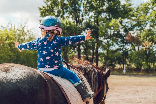 Little kid riding on a horse with their arms outstretched